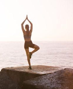 Kvinna gör yoga vid havet